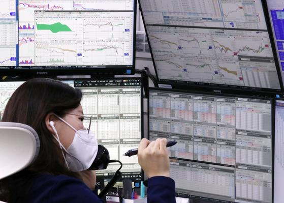19일 서울 영등포구 여의도 국민은행 딜링룸에서 한 직원이 전화 통화를 하며 컴퓨터 화면을 바라보고 있다. 연합뉴스