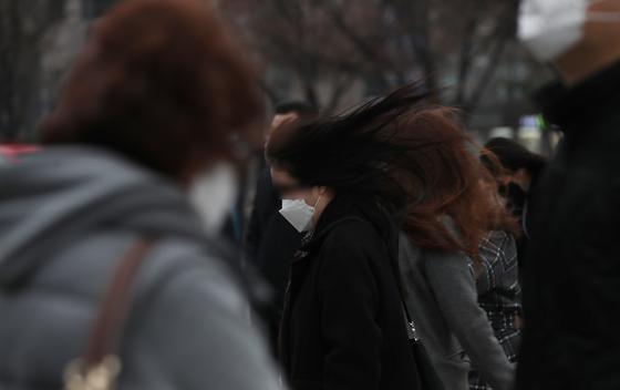 춘분을 하루 앞두고 전국에 태풍급 강풍이 예보된 19일 오전 서울 광화문 네거리에서 시민들이 출근길 발걸음을 재촉하고 있다. 뉴시스