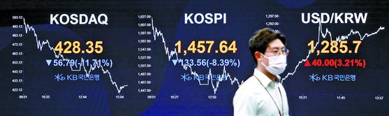 코스피가 전일보다 8.39% 급락해 1457.64로 마감한 19일 오후 서울 여의도 KB국민은행 딜링룸에서 한 관계자가 이동하고 있다. 김성룡 기자