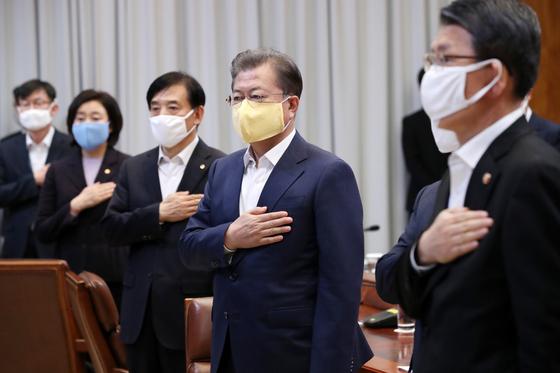 19일 청와대관에서 열린 제1차 '비상경제회의'에서 문재인 대통령이 노란 면마스크를 쓰고 국민의례를 하고 있다. 강정현 기자
