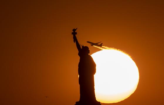 미국 뉴욕의 상징인 자유의 여신상 뒤로 항공기가 이륙하고 있다. 미 국무부는 현지시간 19일 코로나19 예방을 위해 미국인을 대상으로 세계 모든 국가에 대한 여행금지를 권고했다. 귀국할 수 있는 미국인들은 즉시 귀국하라고 권고했다. [AFP=연합뉴스]