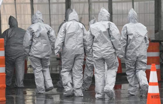 방호복을 입은 작원들이 13일 미국 뉴욕주 뉴 로셀의 신종 코로나 드라이브 스루 진료소로 들어가고 있다. [AFP=연합뉴스]
