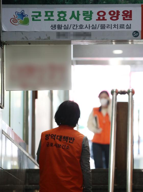 19일 코로나19 확진자가 발생한 경기 군포시의 요양원에 보건소 관계자가 들어서고 있다. [뉴시스]