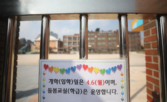 정부가 신종 코로나바이러스 감염증(코로나19) 확산을 막기 위해 전국 유치원과 초·중·고교 개학이 2주일 더 연기를 결정한 지난 17일 서울 용산구의 한 초등학교 교문에 개학연기 안내문이 붙어 있다. [뉴스1]
