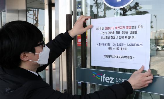 20일 오전 인천시 연수구 송도국제도시 G타워 에서 직원이 건물 폐쇄 안내문을 붙이고 있다. [뉴시스]