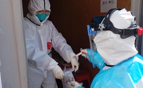 대구 영남대병원 드라이브 스루 선별진료소에서 간호사들이 검사 대상자들을 상대로 채취한 검체를 지퍼락에 밀봉하고 있다. 연합뉴스