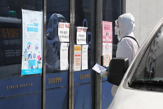 20일 오후 26명의 신종 코로나바이러스 감염증(코로나19) 확진자가 발생한 대구 수성구 중동 김신요양병원 앞에서 119구급대원이 내부로 들어가기 위해 기다리고 있다. 뉴스1