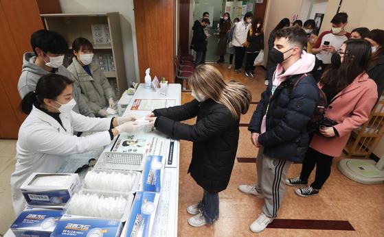 16일 오후 경기도 수원시 경기대학교 건강증진센터에서 외국인 유학생들이 마스크를 받고 있다. [연합뉴스]
