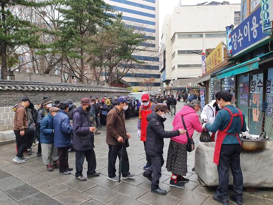 17일 서울 탑골공원의 한 무료급식소 앞에 사람들이 줄을 서서 음식을 기다리고 있다. 김홍범 기자