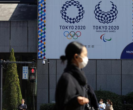 마스크를 쓴 여성이 9일 오후 도쿄 올림픽·패럴림픽 홍보물이 설치된 일본 도쿄도(東京都) 지요다(千代田)구의 한 사거리를 지나가고 있다. [연합뉴스]