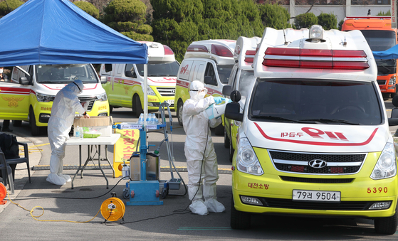 22일 오전 대구시 달서구 옛 두류정수장에서 119 구급대원이 신종 코로나바이러스 감염증(코로나19) 환자 이송에 투입된 119 앰뷸런스를 소독하고 있다. [연합뉴스]