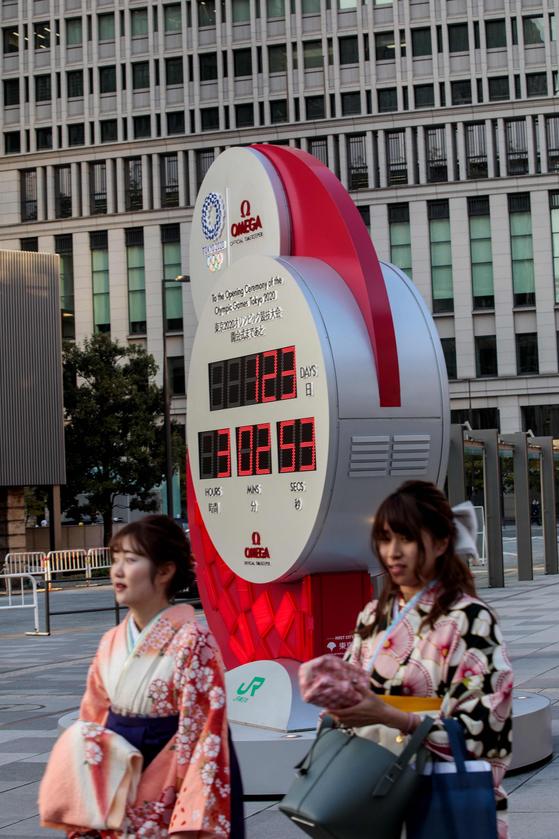 지난 23일 도쿄역 앞에 설치된 올림픽 카운트다운 전광판을 지나는 도쿄 시민들. [로이터=연합뉴스]