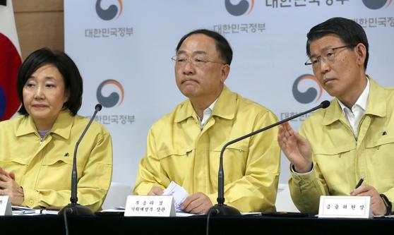 홍남기 부총리 겸 기획재정부 장관(가운데)이 19일 오후 정부서울청사에서 열린 비상경제회의 개최 결과 브리핑에서 기자들의 질문을 듣고 있다. 연합