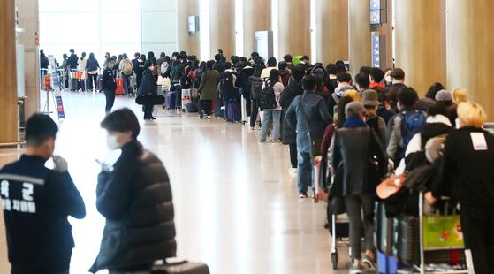 23일 인천국제공항 1터미널에서 독일 프랑크푸르트 발 여객기를 타고 입국한 승객들이 격리시설로 이동하는 버스를 탑승하기 위해 줄지어 기다리고 있다. 뉴시스