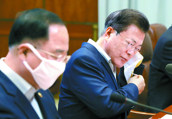 문재인 대통령(왼쪽 두 번째)이 19일 청와대에서 코로나19 대응 논의를 위한 1차 비상경제회의 발언을 위해 마스크를 벗고 있다. [청와대사진기자단]