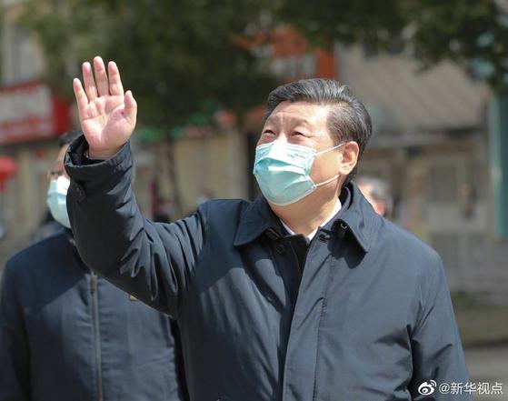 시진핑 중국 국가주석이 지난 10일 신종 코로나 사태 이후 처음으로 우한을 찾아 여전히 집에 갇혀 생활하는 아파트 주민을 향해 손을 흔들어 인사하고 있다. [중국 신화망 캡처]