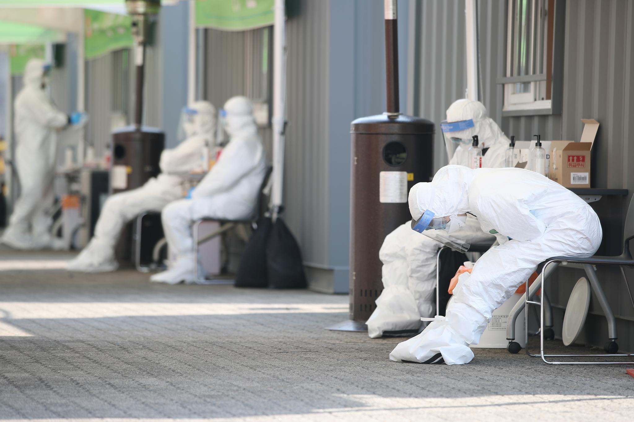23일 오후 서울 송파구 잠실야구장에 설치된 드라이브 스루 선별진료소에서 의료진이 의자에 앉아 잠시 쉬고 있다. 연합뉴스