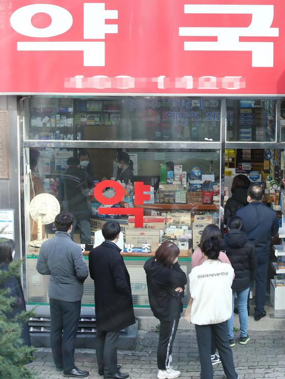 공적 마스크 판매처와 수량을 실시간으로 알려주는 애플리케이션과 웹 서비스가 시작된 11일 오후 서울 시내 한 약국에서 시민들이 마스크를 구매하기 위해 줄을 서 있다. [연합뉴스]