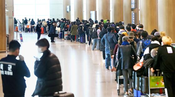 정부가 코로나19 관련 유럽발 입국자에 대한 검역을 강화한 가운데 23일 인천국제공항 1터미널에서 독일 프랑크푸르트 발 여객기를 타고 입국한 승객들이 격리시설로 이동하는 버스를 탑승하기 위해 줄지어 기다리고 있다.[뉴시스]