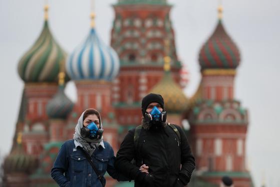 마스크를 쓴 채 러시아 모스크바 붉은 광장 근처를 걷고 있는 젊은이들. [연합뉴스]
