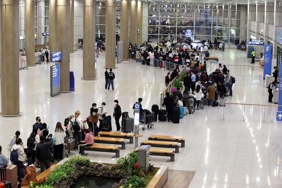 유럽에서 국내로 들어오는 모든 입국자 전원을 대상으로 신종 코로나바이러스 감염증(코로나19) 진단 검사를 시작한 22일 오후 유럽발 입국자들이 인천공항을 통해 귀국해 검사를 위해 길게 줄을 서 있다. 유럽발 입국자 중 유증상자는 검역소 격리시설에서, 무증상자는 지정된 임시생활시설에서 검사를 받는다.뉴스1