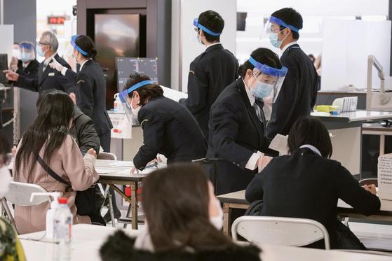 지난 21일 일본 지바현 나리타공항에서 마스크와 안면 보호장비를 착용한 검역 요원들이 독일에서 입국한 사람들의 서류 작성을 돕고 있다. 일본 정부는 독일 등 유럽 15개국을 입국거부 대상으로 추가할 방침이다. [AP=연합뉴스]