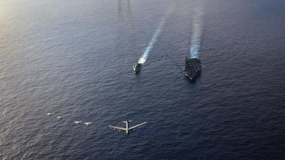 지난 21일 필리핀해에서 미국 공군과 합동 훈련 중인 시어도어 루스벨트함(CVN 71). B-52 전략폭격기가 F-15C 전투기의 호위를 받으며 선두를 이끌고 있고, 시어도어 루스벨트함(오른쪽)과 이지스 순양함인 벙커힐함(CG 52)이 따르고 있다. [사진 미 해군]