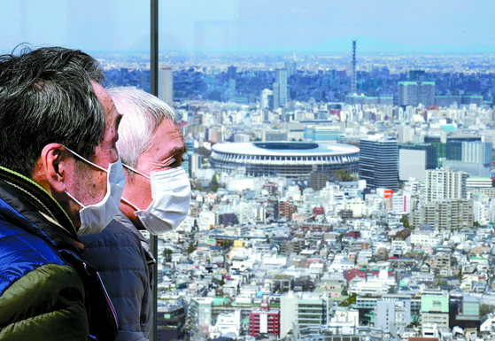 아베 신조 일본 총리와 토마스 바흐 국제올림픽위원회(IOC) 위원장이 24일(현지시간) 올 7월 열릴 예정이었던 도쿄 올림픽·패럴림픽을 1년 정도 연기 하기로 했다. 이날 마스크를 착용한 노부부 오른쪽으로 도쿄 올림픽과 패럴림픽의 주 경기장이 보인다. [EPA=연합뉴스]