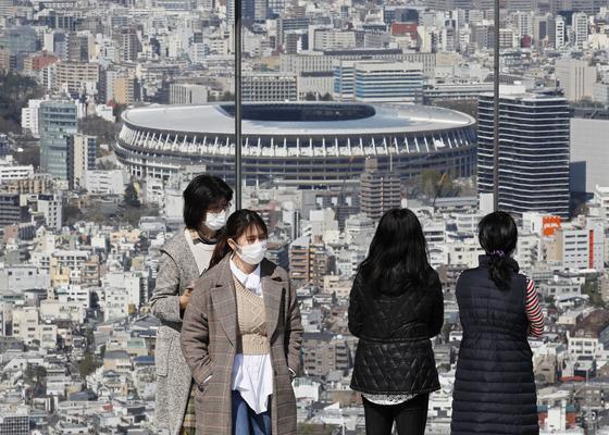 지난 24일 일본 도쿄의 한 전망대에서 마스크를 쓴 관광객들이 도쿄올림픽 메인스타디움을 바라보고 있다. 일본 정부가 이날 밤 도쿄올림픽 연기를 전격 발표한 가운데 25일 도쿄에선 하루 최다 신종 코로나 확진자가 발생했다.[EPA=연합뉴스]