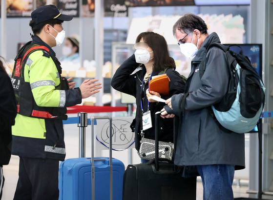 24일 인천국제공항 제2터미널에서 영국 런던발 여객기를 타고 입국한 외국인 승객들이 신종 코로나바이러스 감염증(코로나19) 진단 검사를 받기 전 경찰 관계자에게 안내를 받고 있다. [뉴스1]