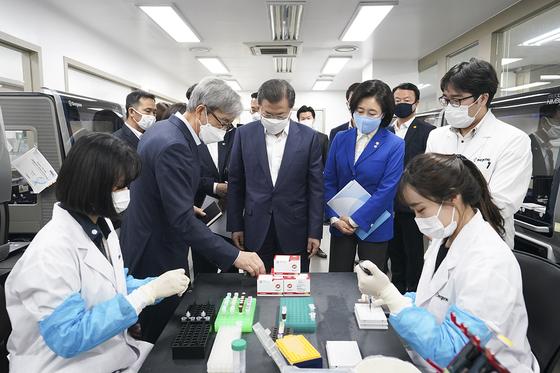 문재인 대통령이 25일 서울 송파구 신종 코로나바이러스 감염증(코로나19) 진단시약 긴급사용 승인 기업을 방문, PCR셋업준비실에서 천종윤 씨젠 대표와 시약에 대해 대화를 나누고 있다. [사진 청와대]