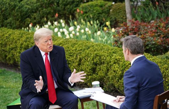 """도널드 트럼프 미국 대통령이 24일(현지시간) 백악관 로즈가든에서 폭스뉴스와 인터뷰하고 있다. 이 자리에서 트럼프 대통령은 """"부활절 전까지 경제 활동을 재개하겠다""""고 밝혔다. [AFP=연합뉴스]"""