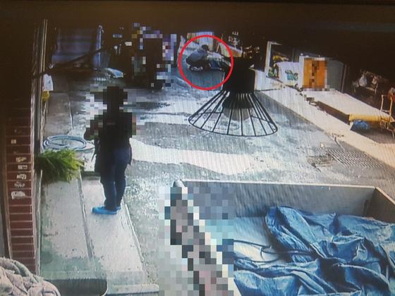 지난해 10월 11일 오후 4시9분쯤 전북 전주시 완산구 한 전통시장 골목에서 한 여성(빨간 원)이 가게 앞에 쓰러진 남편 B씨(49)의 상처 부위를 막으며 지혈하고 있다. B씨는 형 A씨(59)가 휘두른 흉기에 찔려 숨졌다. [인근 가게 CCTV 캡처]