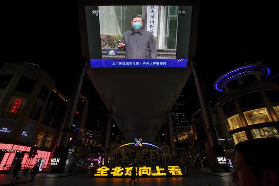 지난 10일 시진핑 중국 국가주석의 우한(武漢) 시찰 뉴스가 방영되는 베이징 쇼핑몰의 초대형 전광판 아래로 한 시민이 지나고 있다. 중국의 선전 기구들은 이날부터 일제히 팬데믹 이 시작된 우한을 방문한 시 주석의 모습을 대대적으로 선전했다. [AP=연합뉴스]