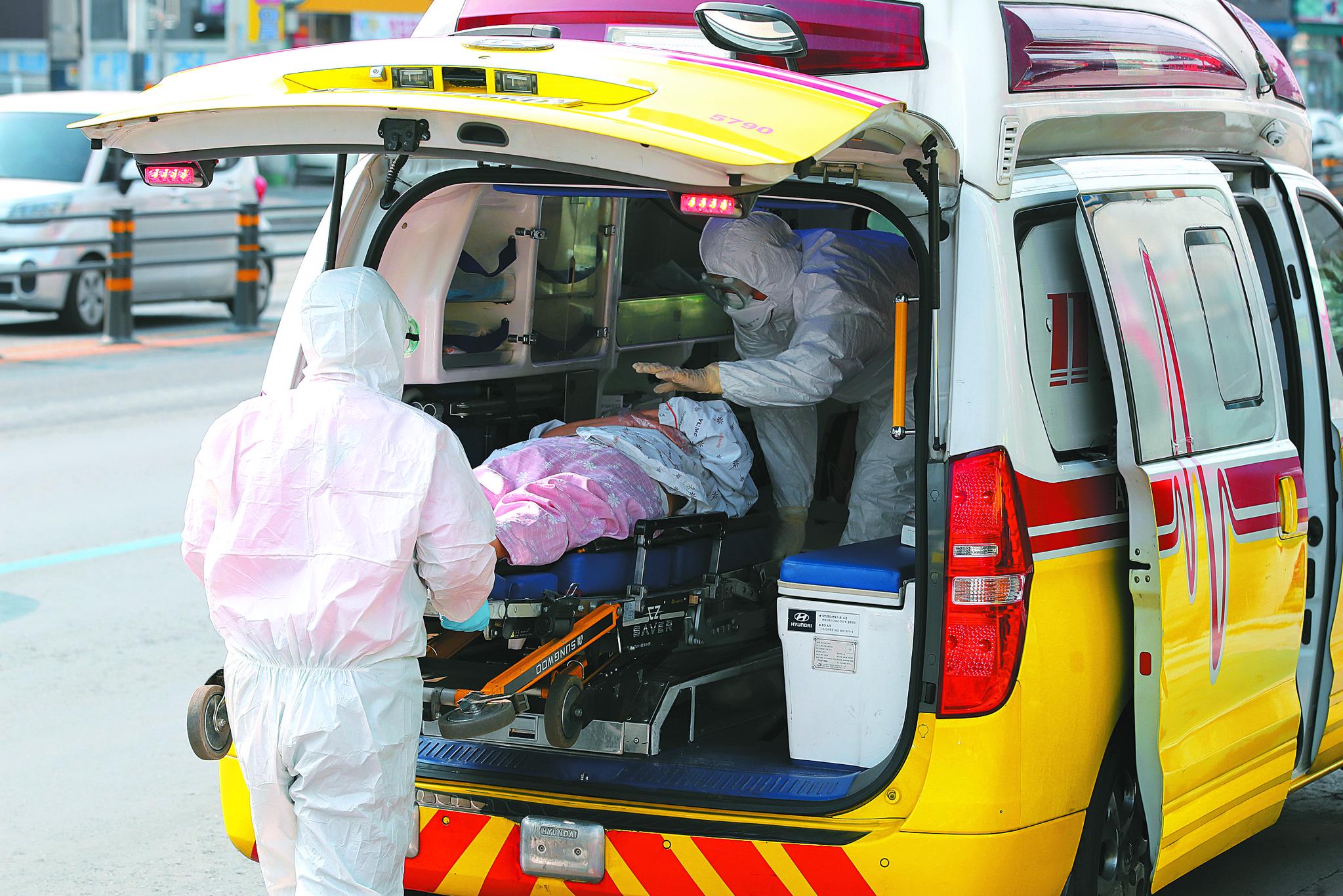 환자와 직원 등 70여 명의 신종 코로나바이러스 감염증(코로나19) 확진자가 발생한 대구 서구 비산동 한사랑요양병원에서 19일 오전 보호복을 착용한 119구급대원이 확진자를 구급차에 태우고 있다. 뉴스1