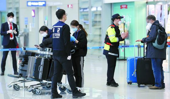 영국 런던발 항공편으로 입국한 외국인들이 24일 오후 인천국제공항 2터미널에 도착해 임시생활시설로 향하는 버스를 타기 위해 이동하기 전 경찰과 육군 현장 지원팀의 설명을 듣고 있다. 연합뉴스