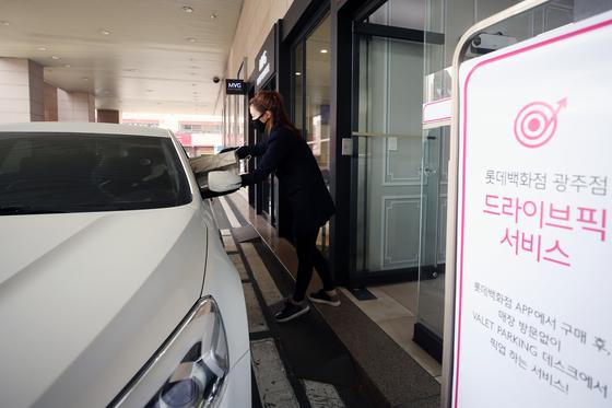 지난 19일 오전 광주 동구 롯데백화점에서 한 고객이 미리 주문한 물건을 자신의 차량에서 건네받고 있다. 롯데백화점 광주점은 이달 17일부터 코로나19 확산에 효율적으로 대응하기 위해 '드라이브-픽'(차량 이동형 쇼핑) 서비스를 시작했다. 연합뉴스