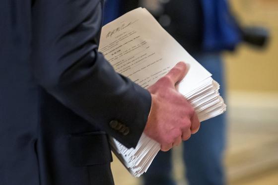 미국 상원에서 25일(현지시간) 한 의회 직원이 미국 행정부와 상원 지도부가 합의한 '코로나19로 인한 긴급 구호 및 경제 보장 법안'을 들고 이동하고 있다. [EPA=연합뉴스]