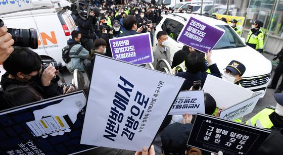 25일 텔레그램의 '박사방' 운영자 조주빈이 탄 차량이 서울 종로경찰서를 나와 검찰 유치장으로 향하자 시민들이 조씨의 강력 처벌을 촉구하며 피켓 시위를 하고 있다. 강정현 기자