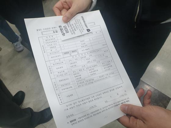 소상공인시장진흥공단 대구 북부센터에서 25일 마지막 대기 번호표인 800번을 받은 상인이 표를 보여 주고 있다. 대구=백경서 기자