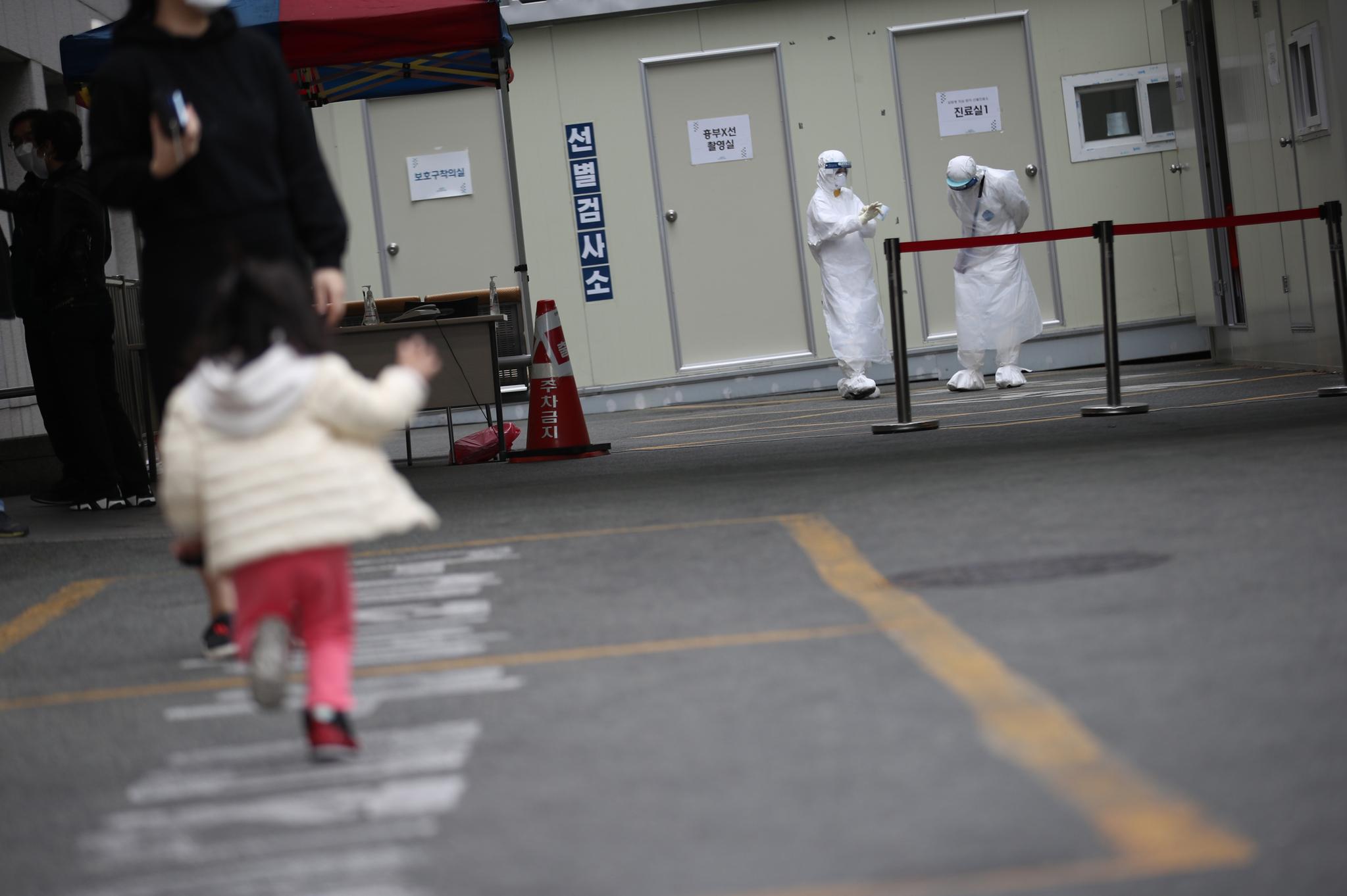26일 오후 신종 코로나바이러스 감염증(코로나19) 확진자가 다수 발생한 것으로 알려진 대구 동구 파티마병원앞에서 대기중인 의료진과 뛰어가는 한 어린이의 모습. 연합뉴스