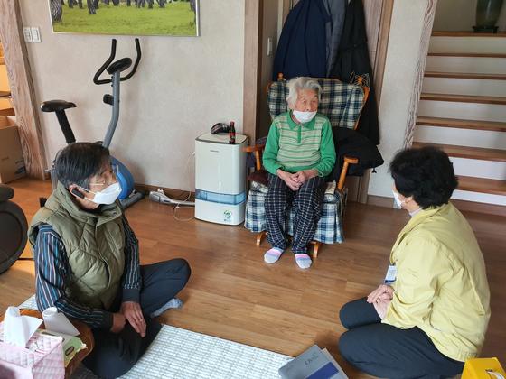 신종 코로나바이러스 감염증(코로나19) 국내 최고령 완치자인 황영주(97) 할머니(가운데)가 아들, 청도군 관계자와 마스크를 쓴 채 이야기를 하고 있다. [사진 청도군]