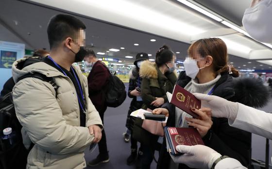 지난달 5일 오전 인천국제공항 1터미널에서 중국발 여객기를 타고 도착한 승객들에게 공항 관계자들이 검역대에서 걷은 여권을 나눠주고 있다. [연합뉴스]