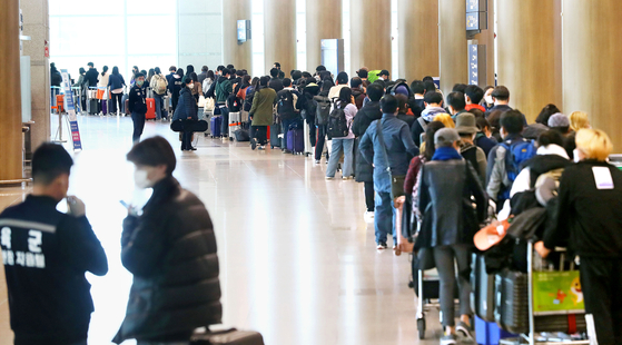 정부가 코로나19 관련 유럽발 입국자에 대한 검역을 강화한 가운데 23일 인천국제공항 1터미널에서 독일 프랑크푸르트 발 여객기를 타고 입국한 승객들이 격리시설로 이동하는 버스를 탑승하기 위해 줄지어 기다리고 있다. 뉴시스