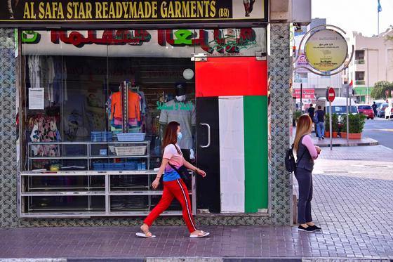 두바이의 한 폐쇄된 가게 앞을 마스크를 쓴 여성이 지나가고 있다.[AFP=연합뉴스]