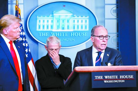 2조 달러에 이르는 최대 규모의 부양책이 25일 미국 상원을 통과했다. 앞서 24일 래리 커들로 백악관 국가경제위원회(NEC) 위원장이 도널드 트럼프 대통령이 지켜보는 가운데 코로나19에 대응한 경기부양책을 설명하고 있다. 가운데는 앤서니 파우치 국립알레르기·감염병연구소장. [AP=연합뉴스]