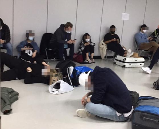 유럽과 미국 등에서 한국으로 입국하면서 인천공항 검역소에서 신종 코로나바이러스 감염증(코로나19) 검사를 받은 입국자 중 유증상자들이 비좁은 공간에서 대기하고 있다. 연합뉴스