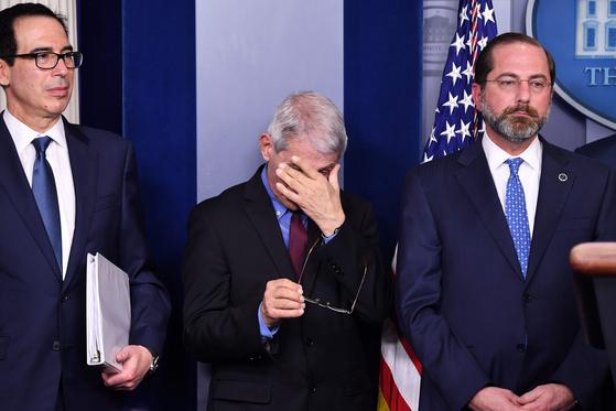 지난 9일 트럼프 대통령이 신종 코로나 기자회견을 하는 옆에서 앤서니 파우치 소장이 피곤한 듯 얼굴을 만지고 있다. [로이터=연합뉴스]