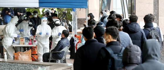 이달 10일 서울 구로구 신도림동 코리아빌딩 앞에 마련된 선별진료소에서 입주자들을 비롯한 주변 직장인들이 코로나19 검진을 받는 모습. 뉴스1