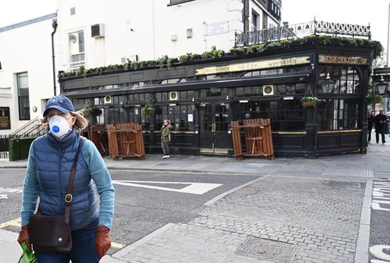 문을 닫은 펍 앞을 지나가는 런던 시민의 모습. 영국에선 지난 23일 불필요한 외출을 금지하는 지침이 내려졌다. EPA=연합뉴스